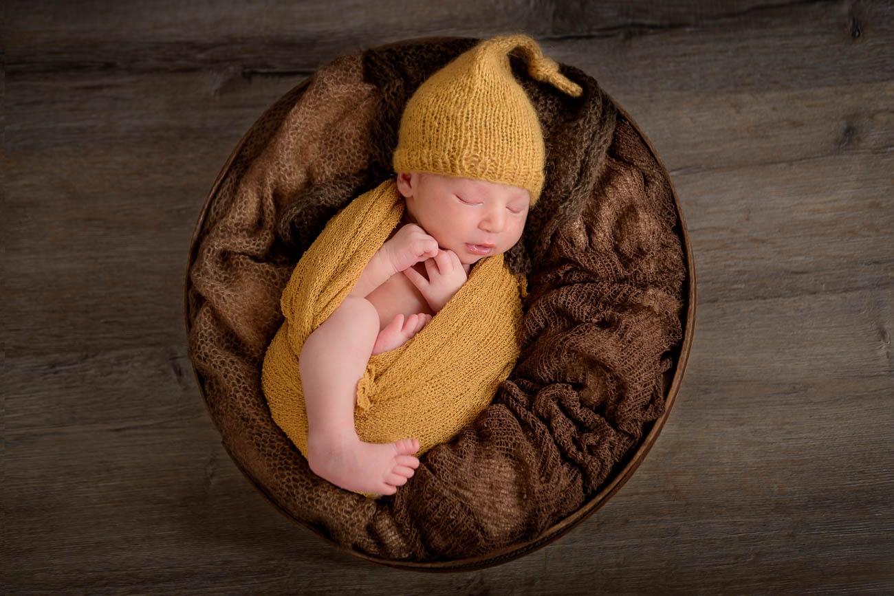neonato che dorme nel cesto durente il servizio fotografico