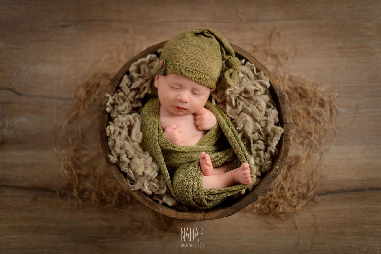 neonato che dorme nella cesta durante servizio fotografico