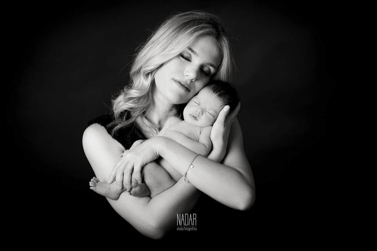 neonato che dorme nella braccia della mamma